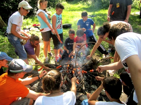 children cooking over a camp fire